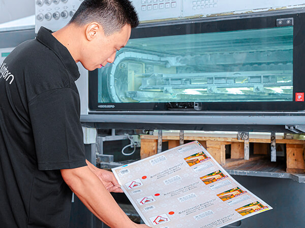 a machine master is checking the packaging boxes' output quality in front of the Heidelberg printing machine